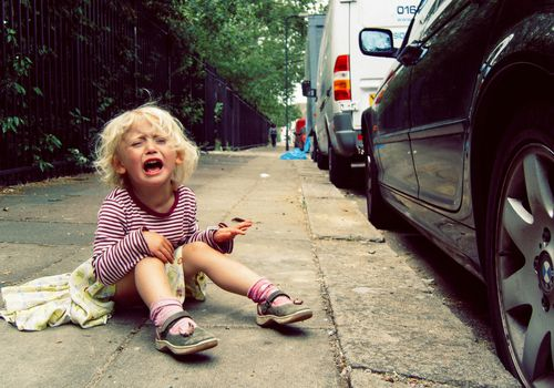 Small girl having a tantrum on the pavement.