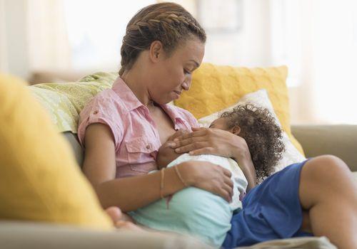 Black woman nursing daughter in living room