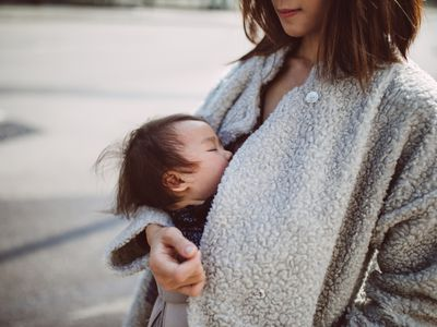 Young mother breastfeeding her baby under a jacket