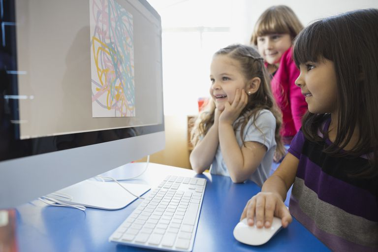 Smiling girls drawing on computer in school
