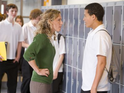 teacher reprimanding a student at school