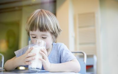 Young child drinking large glass of milk