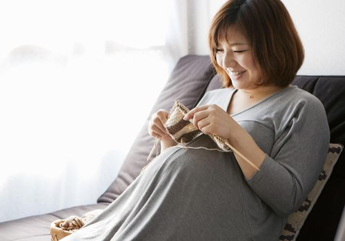 A pregnant woman knitting at home