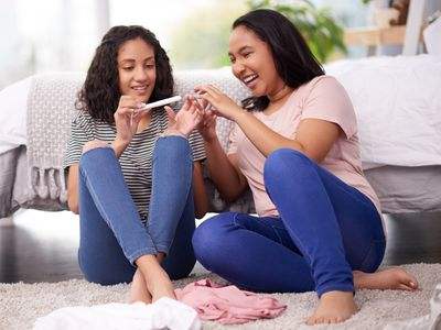 Two teenage girls looking at a tampon
