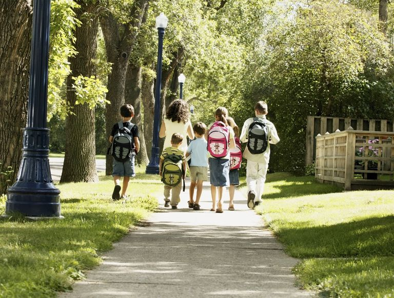 Group of children walking with an adult, wearing backpacks