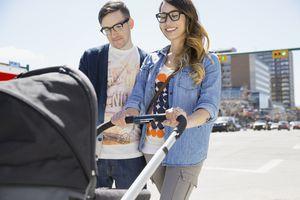 Hipster couple pushing stroller on sunny urban street