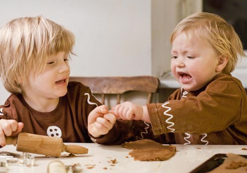 two toddler siblings fighting over playdough at table