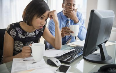Exhausted business people with coffee working at computer