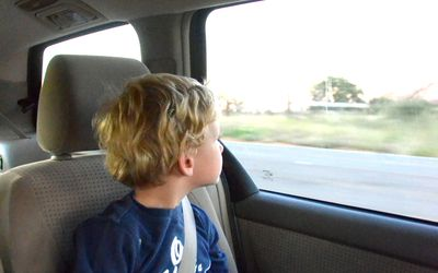 A Child Sitting In Noback Booster Seat Looking Out The Window