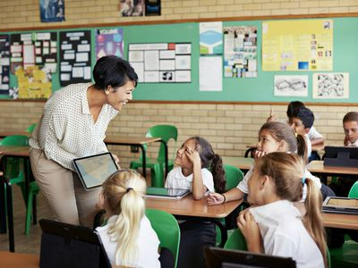 Teacher interacting with kids in class with tablet