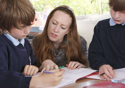 Teacher helping child with work in class