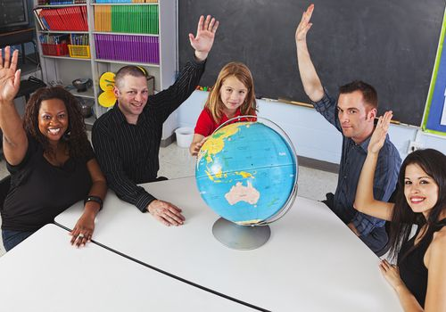 Groups of parents and teachers witha student raising hands around a globe.