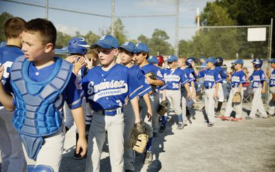 Little League teams congratulating each other after game