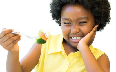 young girl making face eating vegetables