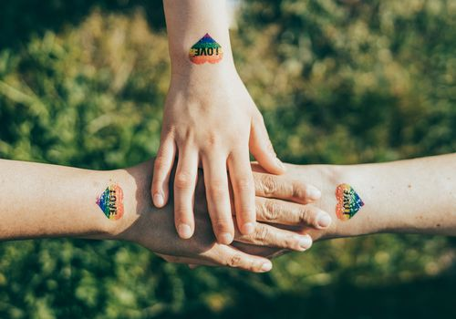 Hands with pride tattoos