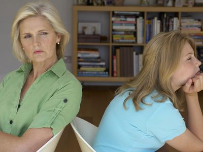 Mother with arms crossed sitting back-to-back with teen daughter
