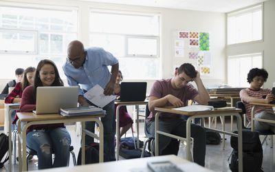 High school teacher helping student at laptop classroom