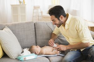 Father using baby wipes while changing his baby's diaper