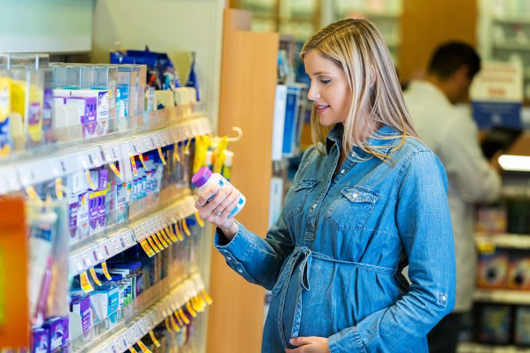 pregnant woman looking at medication in pharmacy aisle