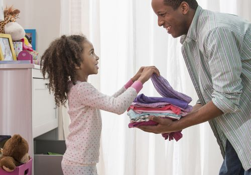 Young girl putting away clean, folded clothes with help from dad.