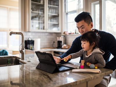Father and daughter using tablet in kitchen