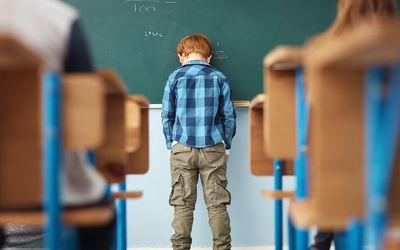 Sad boy at the chalkboard