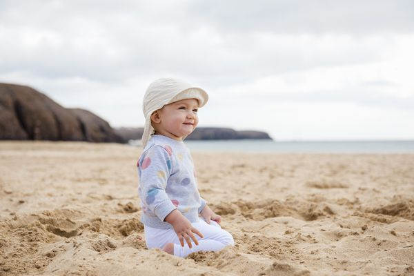 baby wearing a hat at the beach