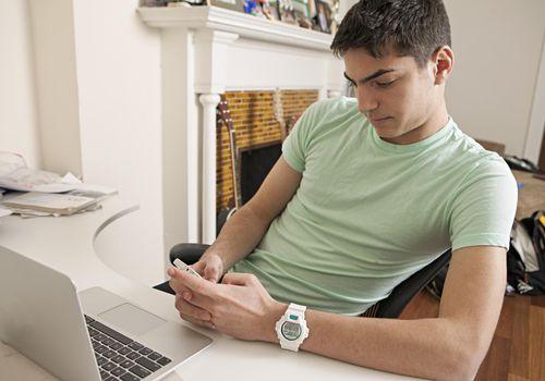 Teen boy using smartphone in front of laptop
