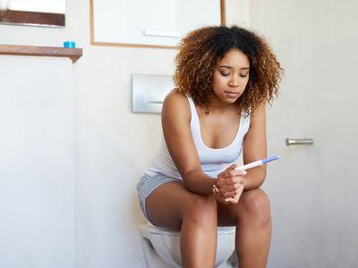 Woman in bathroom looking at pregnancy test