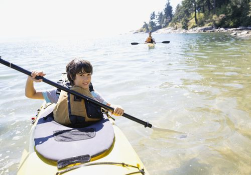 Tween boy kayaking in a lake