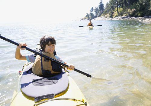 Tween boy kayaking in a lake