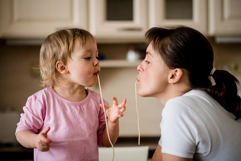 Mother and toddler slurping spagetti