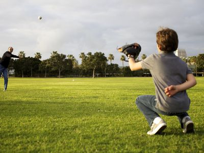 A grandfather throws a baseball to his grandson in a park