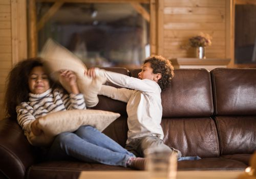 Siblings having fun during a pillow fight on a couch