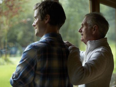 Senior man and adult son looking out window