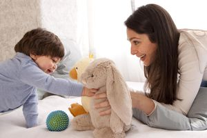Mom and toddler boy playing with stuffed animals