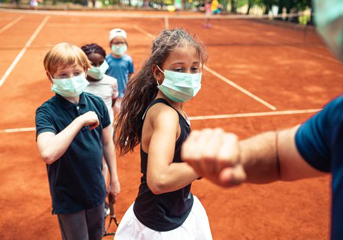 kids on a tennis court wearing masks