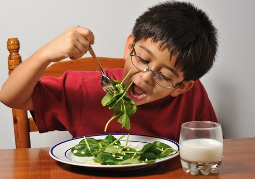 Young boy eating spinach at dinner table