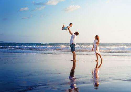 Happy family walking with fun on sunset sea beach