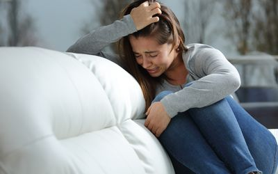 teen girl crying on couch