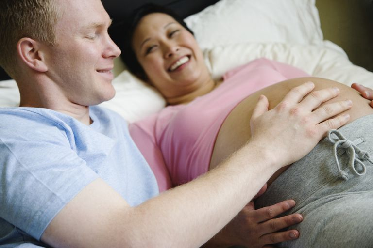 Pregnant couple in bed