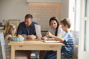 Parents Helping Children With Homework At Kitchen Table