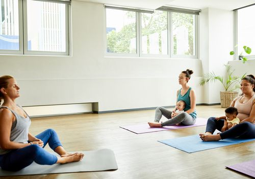 New mothers taking a postpartum yoga class