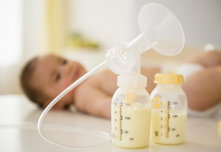 Breast pump and bottles with a baby in the background
