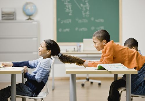 Boy pulling girl's hair in school classroom