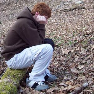 A picture of a boy sulking in the woods