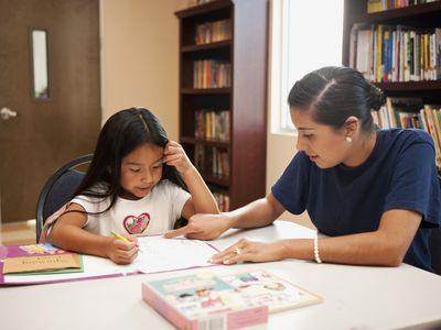 Hispanic woman helping girl with homework in library