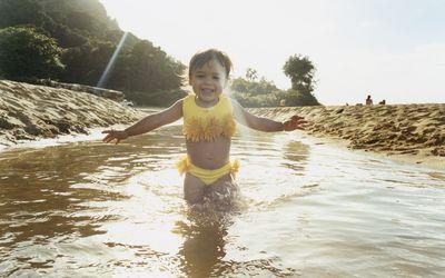 Smiling toddler in yellow bikini on a beach