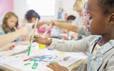 toddlers painting in class
