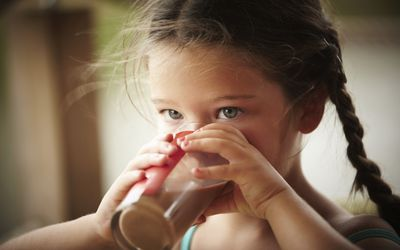 Close up of girl with braids drinking chocolate milk